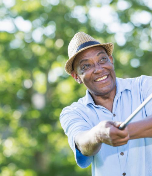 Senior African-American man practicing golf swing